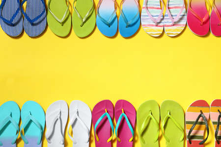 Different flip flops and space for text on yellow background, flat lay. Summer beach accessories
