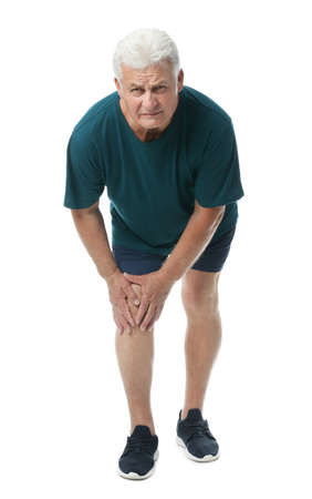 Full length portrait of senior man having knee problems on white background Фото со стока
