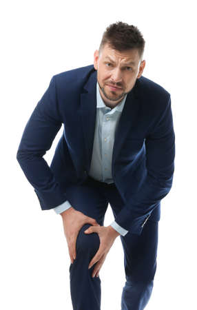 Portrait of businessman having knee problems on white background