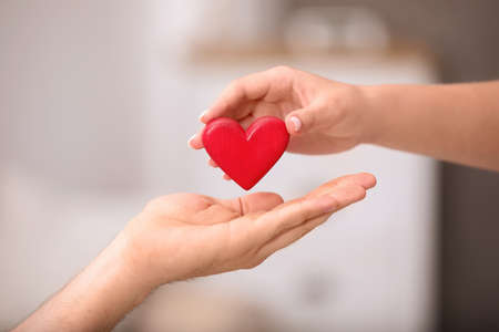 Man giving red heart to woman on blurred background, closeup. Donation concept