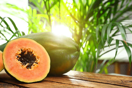 Fresh juicy ripe papayas on wooden table against blurred background, closeup view. Space for text