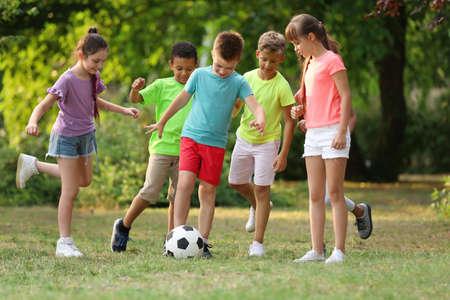 Lindos niños pequeños jugando con una pelota de fútbol en el parque
