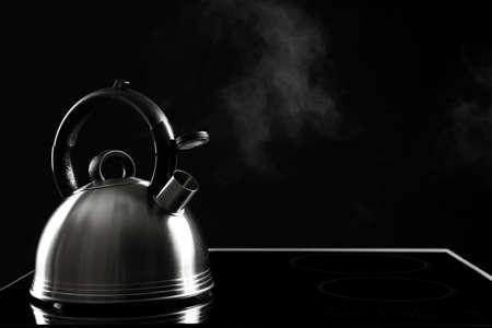 Hervidor moderno con silbato en la estufa contra fondo negro, espacio para texto Foto de archivo