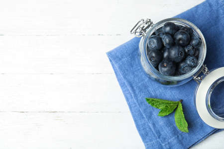 Glass jar of tasty fresh blueberries, mint leaves and fabric on white wooden table, flat lay with space for text