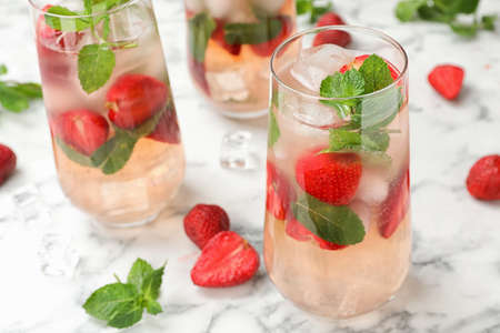 Glasses of refreshing drink with strawberry and mint on marble table, space for text