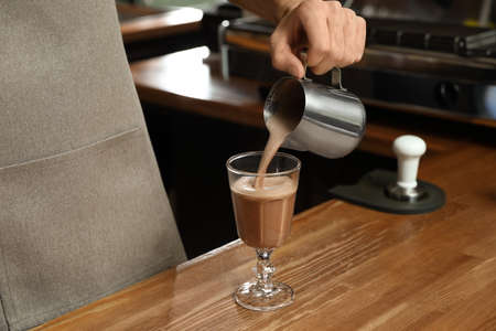 Barista pouring coffee into glass at bar counter, closeup