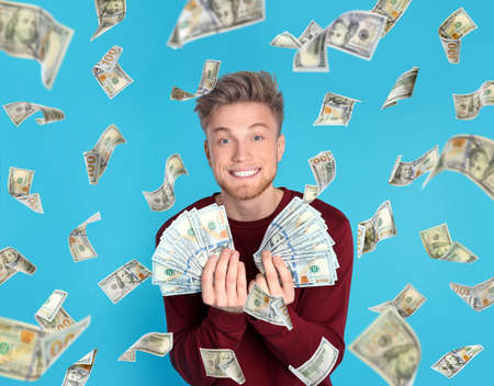Happy young man with dollars under money rain on blue background