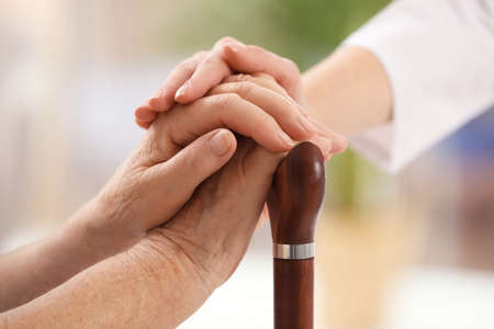 Nurse comforting elderly woman with cane against blurred background, closeup. Assisting senior generation