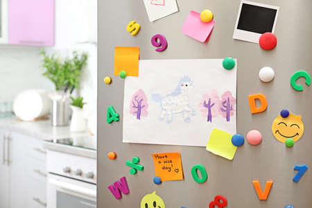 Sheets of paper, child's drawing and magnets on refrigerator door in kitchen. Space for text