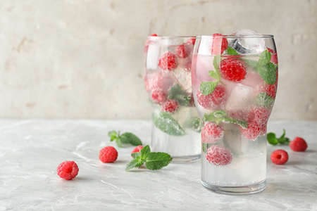 Glasses of refreshing drink with raspberry and mint on grey stone table, space for text