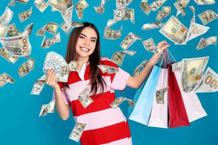 Felice giovane donna con dollari e borse della spesa sotto la pioggia di soldi su sfondo blu Archivio Fotografico
