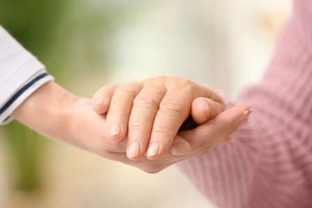 Nurse holding hand of elderly woman against blurred background, closeup. Assisting senior generation Stock fotó