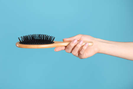 Woman holding wooden hair brush against blue background, closeup