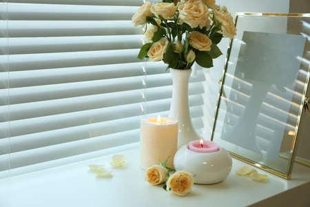 Composition avec bougies allumées, roses fraîches et cadre photo sur le rebord de la fenêtre. Espace pour le texte