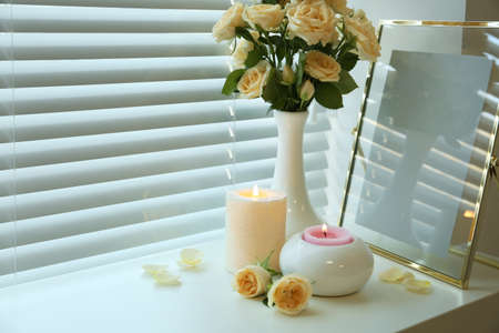 Composition with burning candles, fresh roses and photo frame on window sill. Space for text
