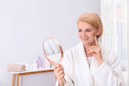 Mature woman with mirror applying face cream at home. Space for text