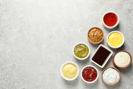 Set of different delicious sauces on grey table, top view. Space for text