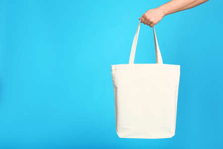 Young man with eco bag on blue background, closeup. Space for text