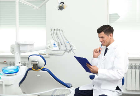 Portrait of professional male dentist with clipboard in clinic. Space for text