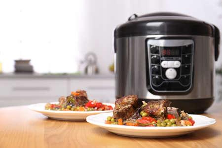 Talerze z mięsem i dodatkami przygotowane w multicookerze na stole w kuchni. Miejsce na tekst Zdjęcie Seryjne