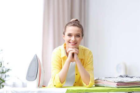 Young pretty woman with iron and clean laundry at board indoors