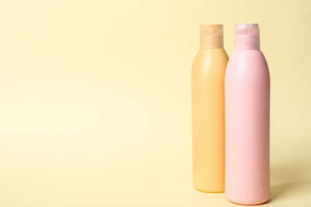 Bottles with cosmetic products on yellow background. Mockup for design