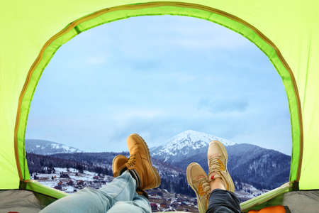 Closeup of people in camping tent on snowy mountain hill, view from inside