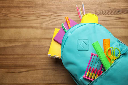 Stylish backpack with different school stationary on wooden table, top view. Space for text