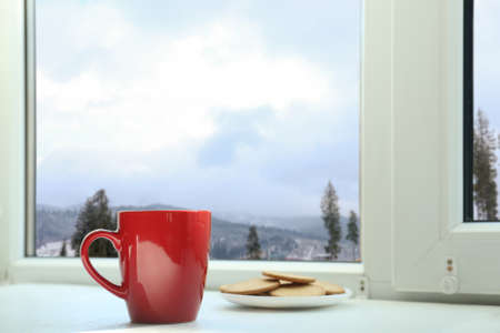 Hot drink and cookies near window with view of winter mountain landscape Foto de archivo