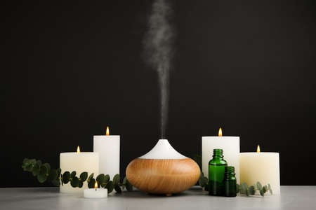 Composition with essential oils diffuser on table against black background. Space for text Stock Photo