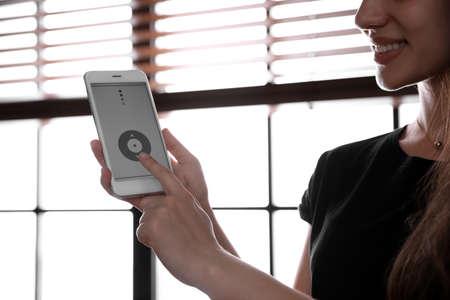 Woman using smart home application on phone to control window blinds indoors, closeup