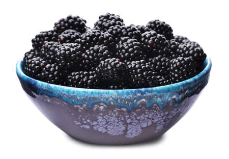 Blue bowl of tasty ripe blackberries on white background