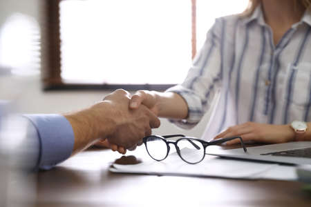 Business partners shaking hands at table after meeting in office, closeup