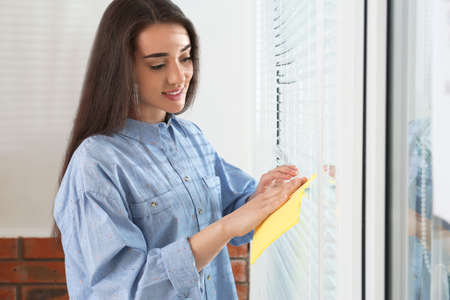 Beautiful woman cleaning window blinds with rag indoors Reklamní fotografie