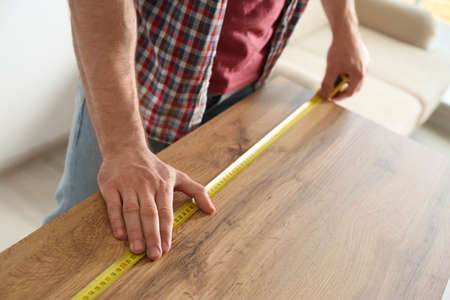 Man measuring wooden table, closeup. Construction tool