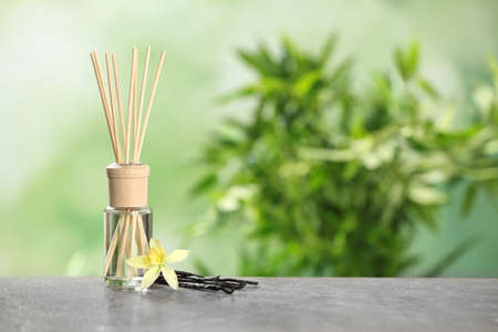 Reed air fresher with vanilla flower and sticks on grey table against blurred green background. Space for text