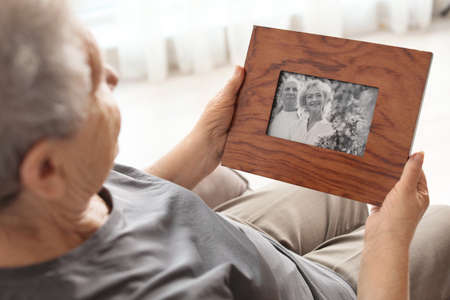 Elderly woman with framed family portrait at home Stock fotó