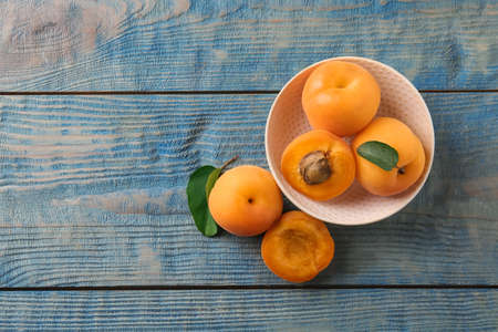 Composition with delicious apricots on blue wooden background, top view. Space for text