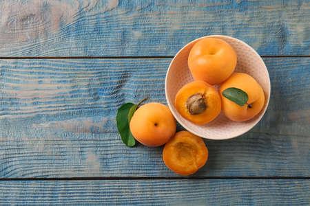 Zusammensetzung mit köstlichen Aprikosen auf blauem hölzernem Hintergrund, Draufsicht. Platz für Text