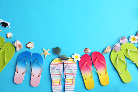 Flat lay composition with different flip flops on blue background, space for text. Summer beach accessories