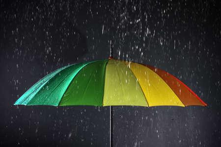 Bright umbrella under rain on dark background Imagens