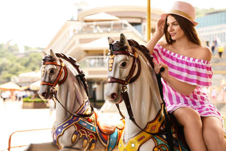 Young pretty woman riding carousel in amusement park
