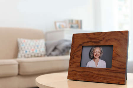 Framed portrait of senior woman on table indoors. Space for text