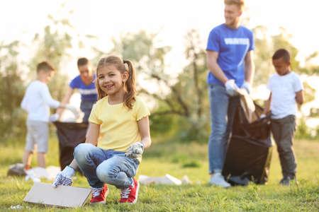 Bambina che raccoglie rifiuti nel parco. Progetto di volontariato