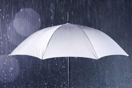 White umbrella under rain on dark background