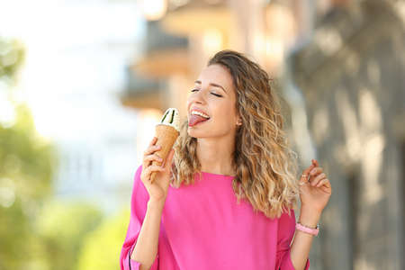 Happy young woman with delicious ice cream in waffle cone outdoors