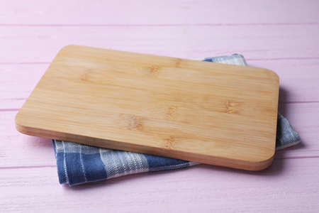 Kitchen towel and cutting board on pink wooden table 免版税图像