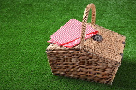 Checkered tablecloth and closed wicker picnic basket on green grass, space for text Stock Photo