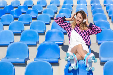 Happy girl with retro roller skates sitting on grandstand