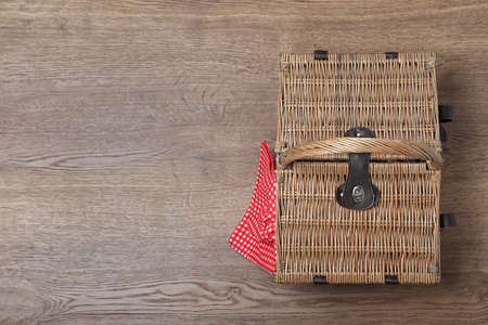 Geschlossener Weidenpicknickkorb auf Holztisch, Draufsicht. Platz für Text